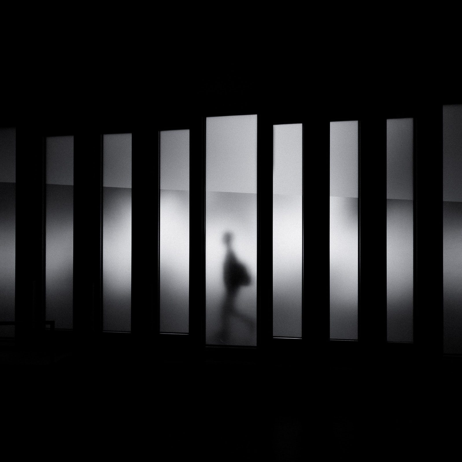 A shadowy window with a dancer behind it. This image is in black and white